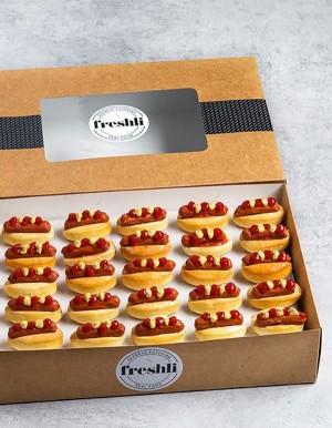 Box de 25 unidades de mini hot dogs con kétchup y mostaza.