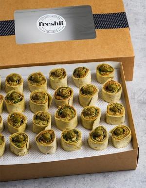 Box de 24 unidades de mini wrap roll de caviar de berenjena, falafel y rúcula  en pan blanco.