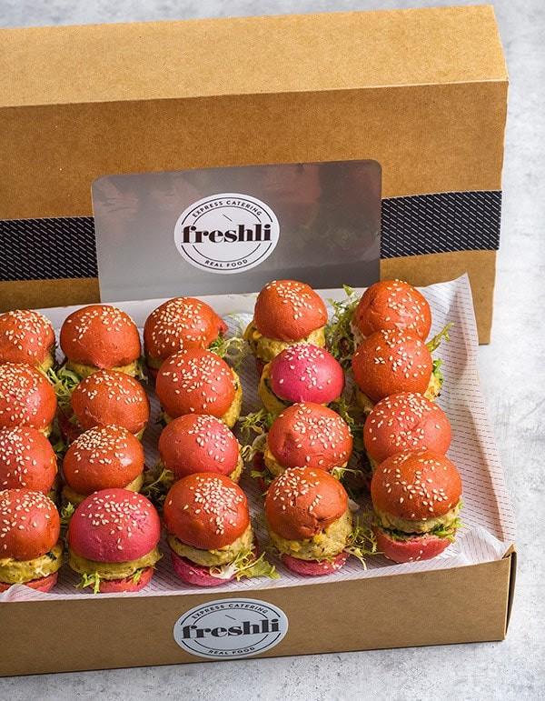 Box de 20 unidades de mini burgers de pollo con brotes de espinacas en pan de espinacas.