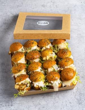 Box de 16 unidades de mini focaccia de pollo al horno con trufa y mango, tomate cherry rojo, rúcula, salsa pesto.