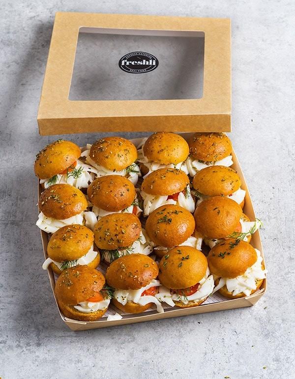 Box de 16 unidades de mini focaccia vegetal con huevo cocido, tomate, lechuga iceberg y mayonesa.