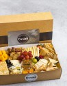 Tabla de quesos: gouda, semi, brie, azul y cheddar, compañados de panes, frutos secos, frutas...